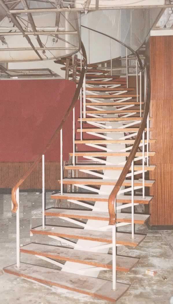 Escalera con curva, escalones y barandas de madera con soporte de